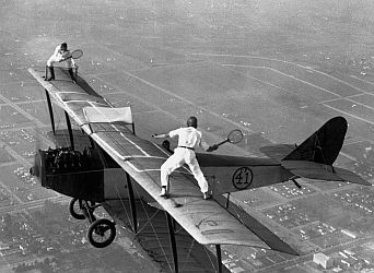 Daredevils playing tennis on a biplane.